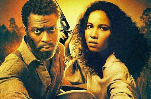 Sepia image of Black man in brown shirt next to Black woman holding black gun and wearing white shirt in front of orange and brown trees and sky