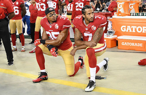 Two Black men in red jerseys with white lettering and gold pants kneel on brown tarp in front of orange drink containers and other men in red jerseys with white lettering