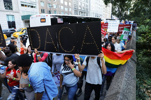 Protestors hold up a black poster that spells out DACA in yellow.