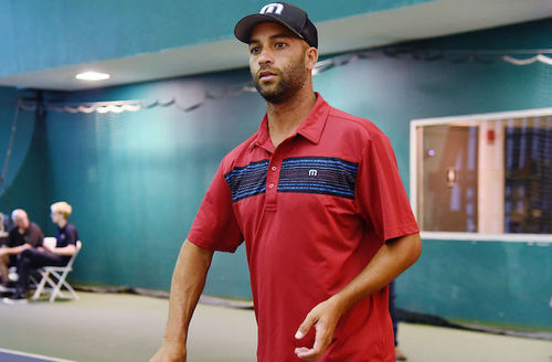 Black man in black baseball cap with white insignia and red collared shirt with navy stripe on grey tennis court in front of teal curtains