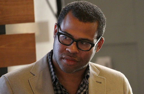 Black man in beige blazer and black and grey checkered shirt and black glasses in front of beige wall and brown wood panels