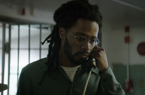 Black man in dark green prison jumpsuit and white shirt holds black telephone in front of blurry dark grey and light grey background