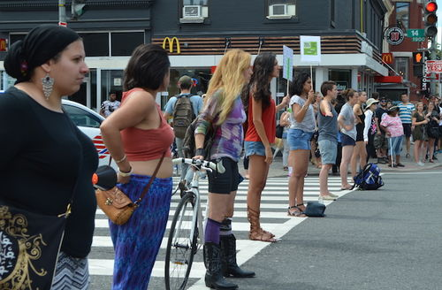 Brown people stand in row on grey street with white traffic markings by brown storefronts