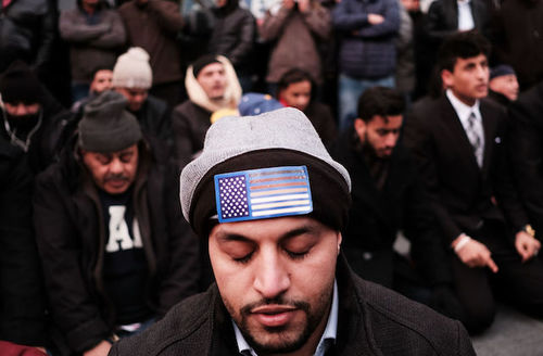 Man wearing black skullcap with American flag on it prays with his eyes closed