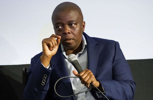 Black man in navy blazer and grey patterned shirt holds black microphone attached to black cable while sitting in black chair in front of grey and black screen
