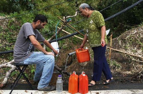 Man fills plastic bottle with water from hose, woman stands nearby holding an organge container