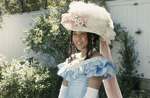 958963048 Black woman in white and blue dress and white gloves and pink hat in front  of