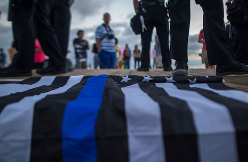 Flag with blue and black and white lines lies on grey stone ground in front of black boot-clad feet and dark blue sky