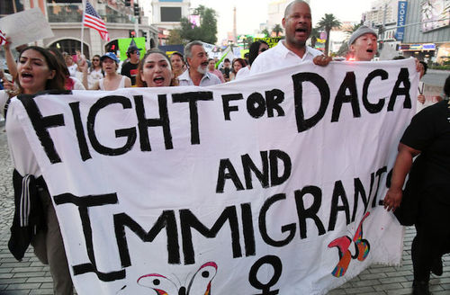 """People marching, carrying a sheet painted with the words, """"Fight for DACA and immigrants."""""""