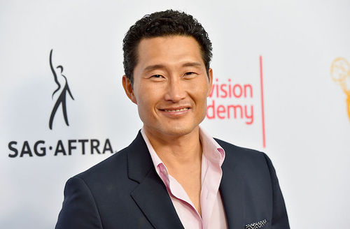 Asian man in dark grey blazer and pink dress shirt in front of light grey wall with black and orange text and insignia