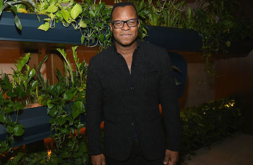 Black man in black suit stands in front of brown wall with black plant pots and green plants