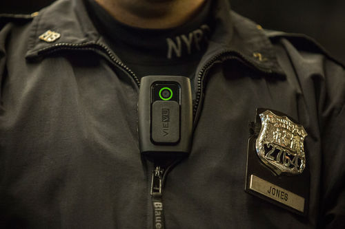 Close-up of a body camera on a White police officer wearing a jacket with a badge that says Jones.