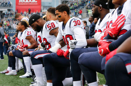 Black men in white uniforms with red and navy lettering and insignia kneel on green grass in front of grey sky