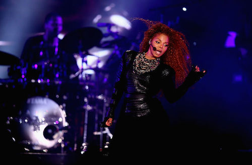 Black woman in black performance outfit in front of blue-lit stage and musicians