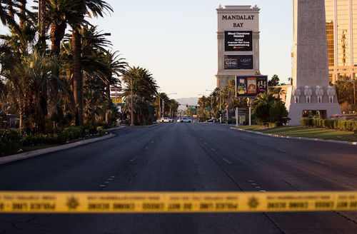 Yellow and black police tape in front of grey cement road with yellow and white lines in front of brown buildings with navy text