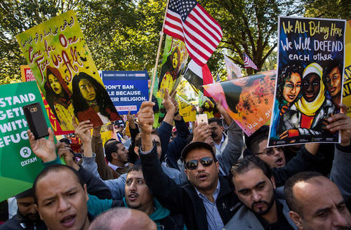 Brown women and men in multicolored clothing hold multicolored signs and red and white and blue U.S. flags in front of