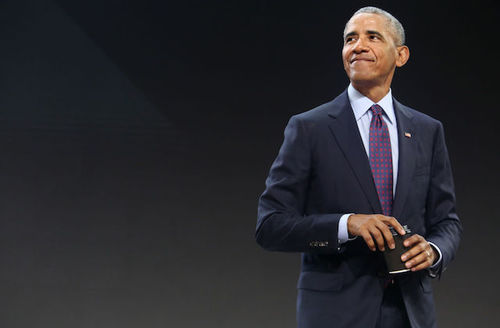 Barack Obama smiles on a stage