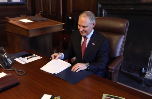 Scott Pruitt. White man smiles at papers on a desk.