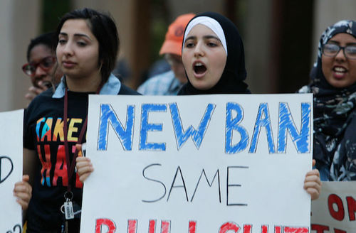 "Protestors, one holds sign that says, ""New ban, same bullshit."""