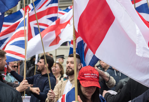 Woman at a protest wearing a red Make America Great Again hat. British flags fly behind her.