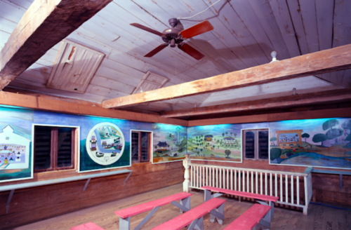 Multicolored murals on brown wood walls near pink benches and white bannister