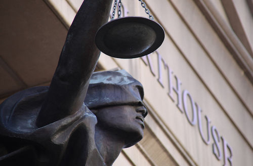 Looking up and southwest at a closeup of the statue of Blind Justice on front of the Albert V. Bryan United States Courthouse in Alexandria, Virginia.