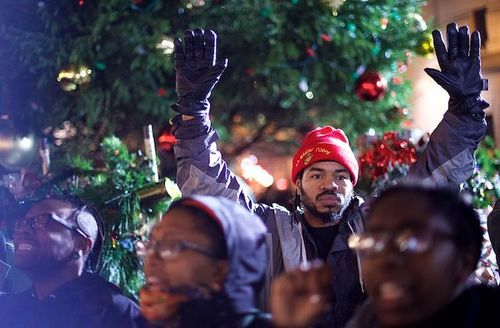 Black man in grey and navy jacket and red hat and black gloves holds up hands behind Black people in multicolored clothing and in front of green Christmas tree and grey building