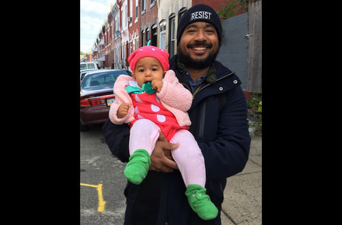 Black man in black jacket and hat holds Black girl in pink jacket and dress with white dots and green shoes in front of grey street and multicolored houses and blue sky