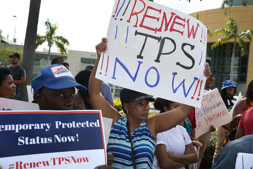 A Black woman at a rally holds a sign above her head that says Renew TPS Now. A Black man next to her holds a sign that says Temporary Protected Status Now.