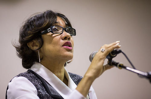 Black woman in black glasses and white shirt and grey patterned vest behind black microphone and stand in front of beige wall