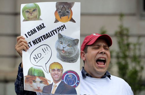 Brown man in red hat and white shirt holds white sign with black text and multicolored images of cats and Brown man in front of grey background