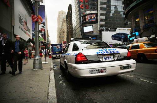 White police car with blue text and black insignia sits on grey street next to brown sidewalk and in front of brown buildings