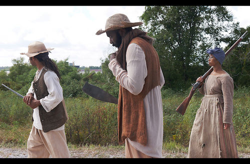 Black man in brown vest holds silver weapon next to Black man in brown vest holding silver machete next to Black woman in brown dress holding brown rifle in front of green field and tree