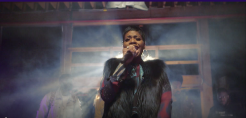 Singer Fantasia performs wearing a black fur vest and a multicolored shirt
