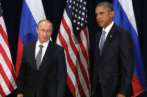 Wihte man in black suit next to Black man in grey suit in front of red white and blue U.S. and Russian flags and black background
