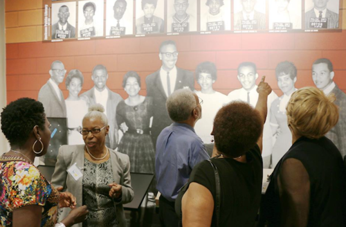 Black women and men in multicolored clothing in front of red exhibit wall with black-and-white portraits of Black people