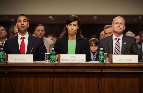 Brown man in navy suit and red tie sits next to White woman in black suit with green shirt next to White man in grey suit with pink striped tie behind brown table with white name tags in front of grey and brown wall