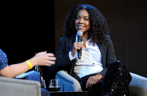 Black woman in black jacket and pants and white blouse holds black microphone and sits in grey chair next to grey chair in front of black background