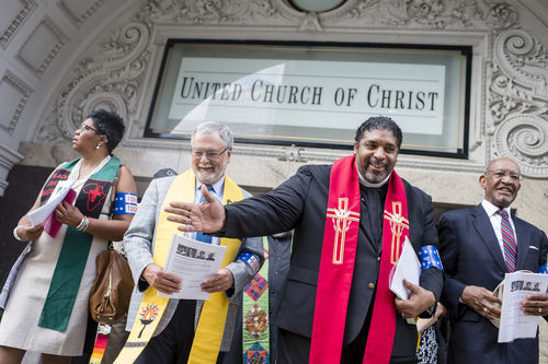 Four faith leaders holding papers standing in front of United Church of Christ.