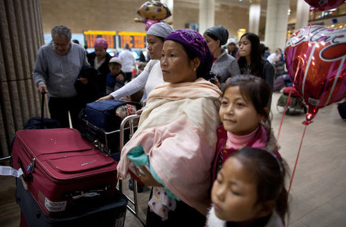 Brown women and girls and men in multicolored clothing stand in brown airport terminal near red and navy suitcases
