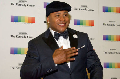 Black man in dark grey hat and tuxedo stands in front of beige wall with black text and multicolored insignia.