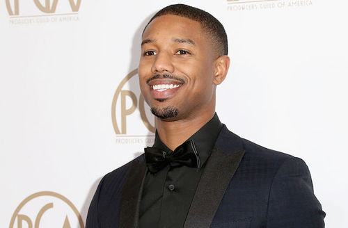 Black man in all-black tuxedo in front of light grey wall with gold insignia