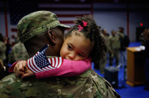 Black man in green and brown camouflage military fatigues holds Black girl in pink sweater holding red and white and blue U.S. flag in front of blurry blue background with women and men in camouflage fatigues