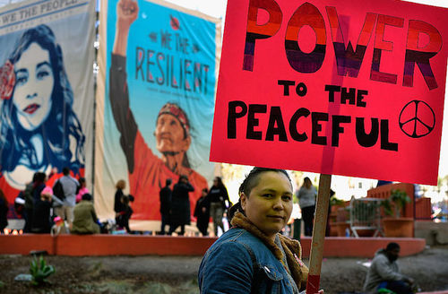 "Woman holds sign that says, ""Power to the peaceful."""