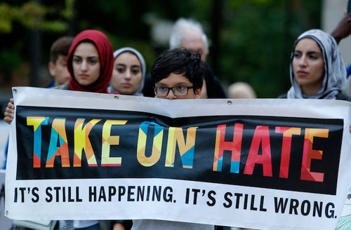 """Protesters hold banner that reads, """"Take on hate. It's still happening. It's still wrong."""""""