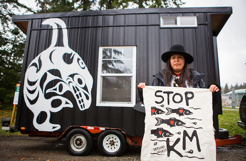 Activist in black hat standing in front of black tiny house holds a white banner with black fish that says Stop KM and Defund Divest