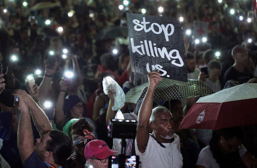 """Protestors, a Black man holds sign that says, """"Stop killing us."""""""