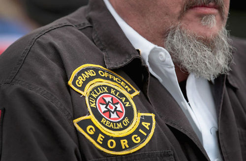 """White man wears patch on jacket that reads, """"Grand officer, Ku Klux Klan, Realm of Georgia."""""""