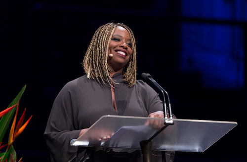 Black woman with blonde dreadlocks wears grey sweater and smiles behind glass stand and black microphones in front of dark grey background