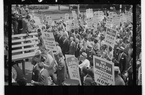Black and white photograph of demonstrators attending a rally and hold signs that say things like